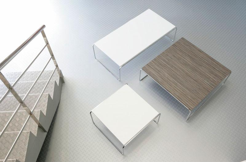 Colección de sofás y mesas de centro y rincón. Sofás disponibles en 1,2 y 3 plazas con cuerpo tapizado y patas metálicas. Mesas disponibles en medidas 120x60x35h, 60x60x35h y 90x90x35h con tapas en melamina color blanco, aluminio o zebrano.